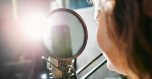 Woman talking into a recording microphone