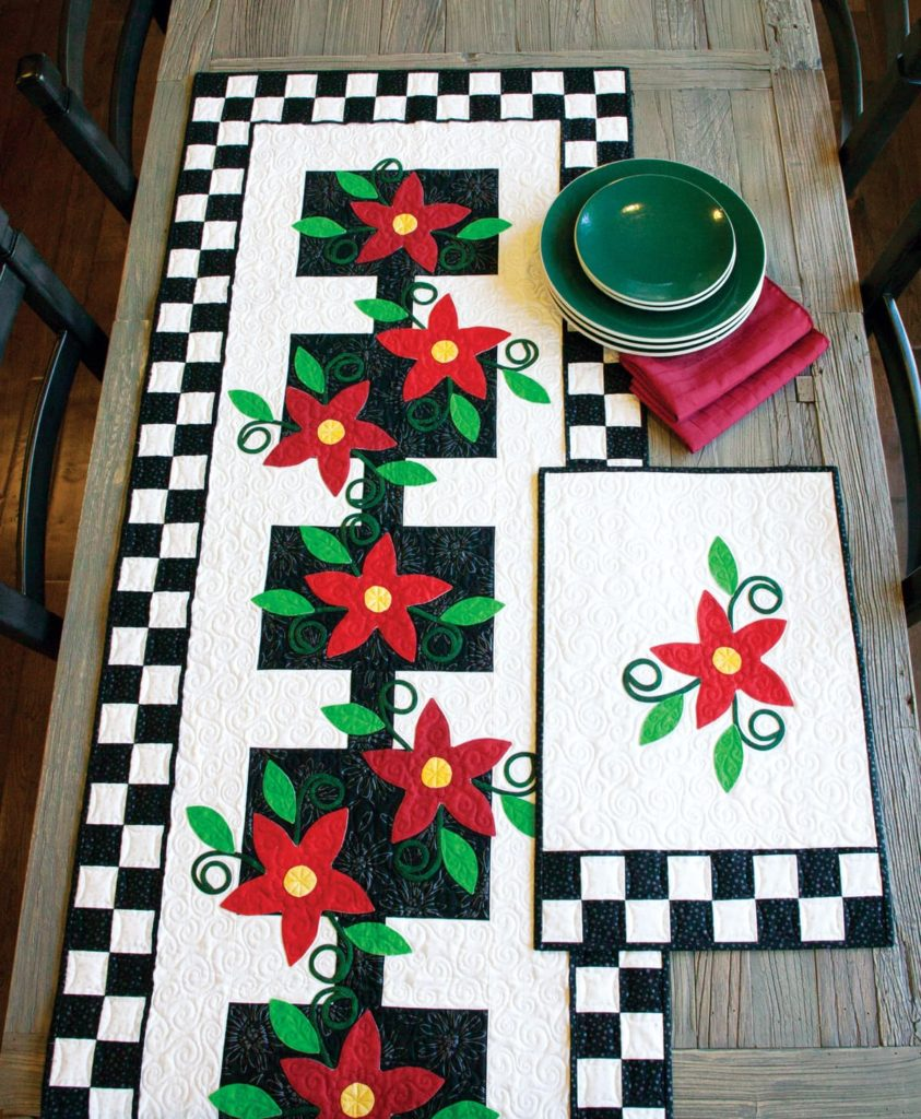 Marcia Harmening's Poinsettia Pizzazz applique quilts table runner and placemats