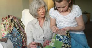 grandmother teaching grandaughter how to quilt for raised by a maker month