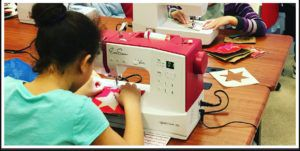 a little girl learning how to sew on a sewing machine