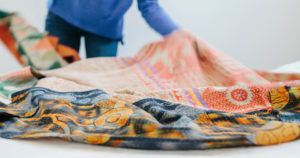 Image of woman spreading colorful fabric over her table