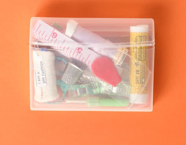 a clear plastic chewing gum case on an orange background that has been converted to a traveling sewing kit.