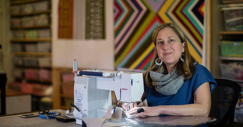 Maria Shell sitting at her sewing machine in her studio in Anchorage with a large quilt hanging up behind her
